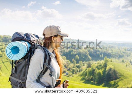 Young hiking woman with backpack and poles enjoying beautiful scene of nature - stock photo