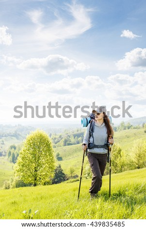 Young hiking woman with backpack and poles walking on green hill - stock photo