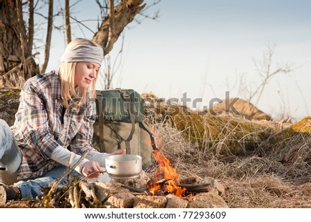 Young hiking woman with backpack cook on campfire in countryside - stock photo