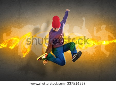 Young hip hop dancer in jump and silhouettes on gray wall