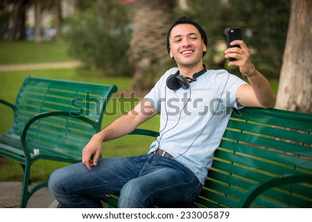 Young hip male taking a selfie at the park - stock photo