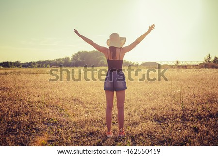 Young hippie woman enjoys sunset