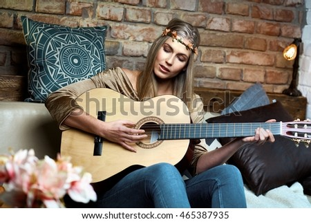 Young hippy girl playing the guitar at home and singing.