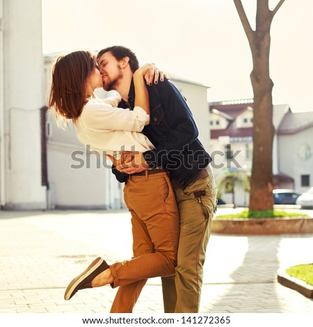 Young hipster beautiful couple in love kissing outdoor in summer on the street - stock photo