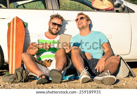 Young hipster best friends having fun with tablet during a car trip moment - Concept of modern technologies and new trends during alternative travel vacation on the road - Nostalgic sunny afternoon - stock photo