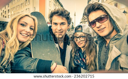 Young hipster best friends taking a selfie in urban city context - Concept of friendship and fun with new trends and technology - Urban alternative everyday life in Berlin european capital - stock photo