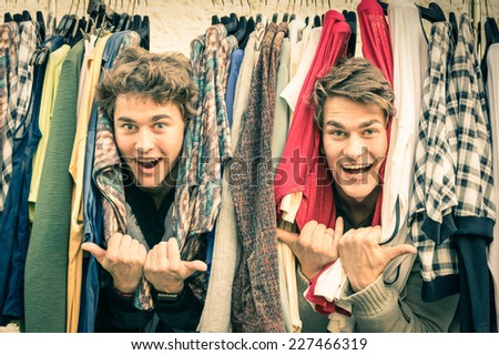 Young hipster brothers at the weekly cloth market - Best friends sharing free time having fun and shopping in the old town in a sunny day - Guys enjoying everyday life moments - stock photo