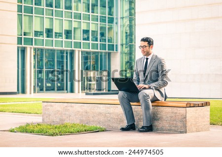 Young hipster business man sitting with laptop at business center - Modern concept of technology wifi connection - Handsome businessman working outdoors with computer connected with wireless internet - stock photo