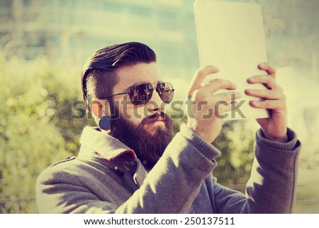young hipster businessman consults his laptop in the heart of city - stock photo