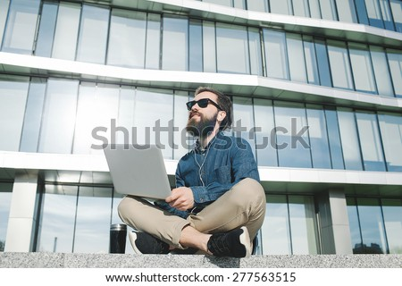 young hipster businessman with beard in sunglasses work with laptop outdoors in front of office building - stock photo