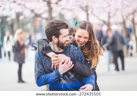Young hipster couple embracing and smiling in Stockholm with cherry blossoms at Kungstradgarden, the swedish for Kings Garden. Love and friendship concepts with a hipster theme. - stock photo