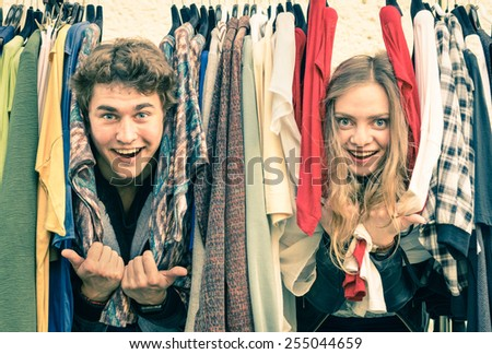 Young hipster couple having at clothing market - Best friends sharing free time and shopping during spring cheap sales - Lovers enjoying everyday life moments on a soft focus and vintage filtered look - stock photo