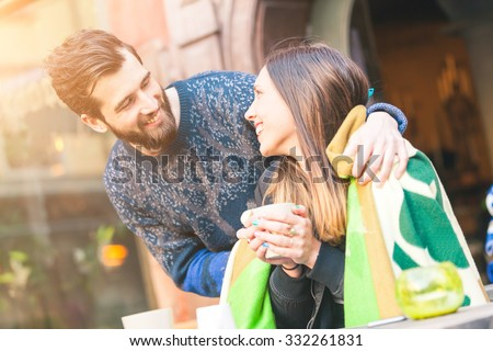 Young hipster couple in a cafe in Stockholm. He puts a blanket on her shoulders, she is holding a cup of hot tea or coffee. They are looking each other smiling. Love or friendship concepts. - stock photo