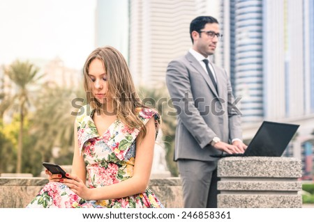 Young hipster couple in a phase of mutual disinterest and sadness - Concept of breaking up connected to the alienation from new technologies - Business man ignoring his girlfriend for working excess - stock photo