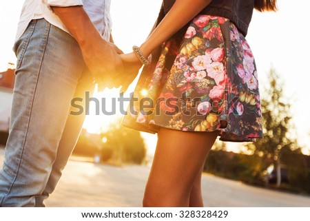 Young hipster couple in love holding hands and looking in sunset. Soft warm  sunny fall colors. Blurred background. Wearing jeans and print skirt.  - stock photo