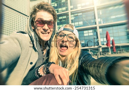 Young hipster couple in love taking a funny selfie in urban city background - Alternative concept of fun and interaction with new trends and technology - Vintage filtered look with blurred edges - stock photo