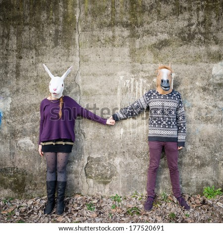 young hipster couple lovers rabbit and horse mask at the park - stock photo