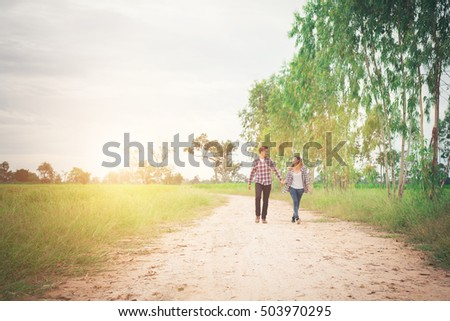 Young hipster couple walking on rural road enjoying with nature, Love couple,holiday traveling, spend time together.
