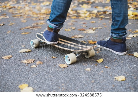 Young hipster fashion guy and his skateboard detail - stock photo