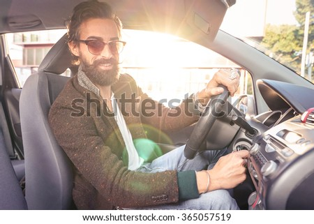 Young hipster fashion model driving car - Young confident man with beard and alternative mustache smiling looking at camera - Lens flare halo is part of composition - Soft vintage marsala filter - stock photo