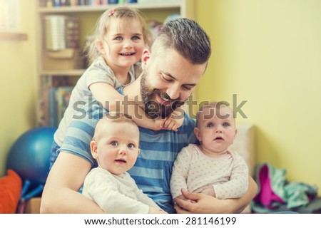 Young hipster father hugging his cute little daughters - stock photo