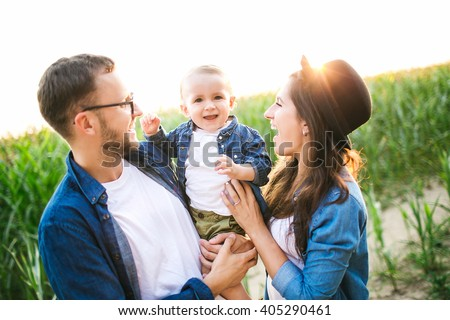 Young hipster father in glasses, mother holding cute baby in summer cornfield - stock photo