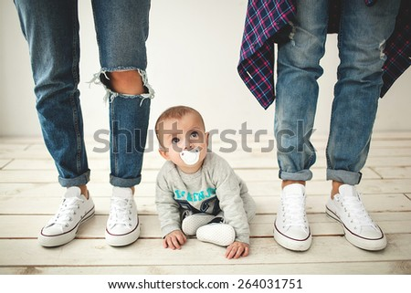 Young hipster father, mother and cute baby boy on rustic wooden floor over white background - stock photo