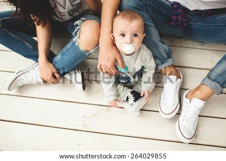 Young hipster father, mother and cute baby boy sitting on rustic wooden floor over white background - stock photo