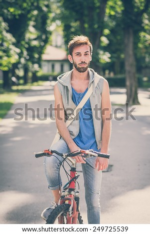 young hipster gay man with bike
