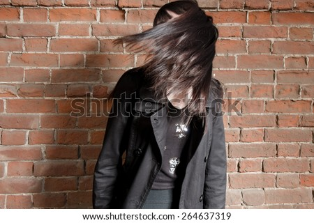 Young hipster gil shake her hairs against red brick wall with copyspace, dishevelled street fashion look - stock photo