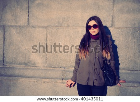 Young hipster girl in grey parka coat and sunglasses spending leisure time outdoors at spring day. Violet and creamy film toning - stock photo