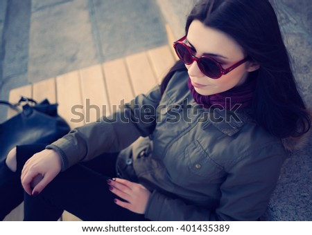 Young hipster girl in grey parka coat and sunglasses spending leisure time outdoors at spring day. Cool blue film toning - stock photo