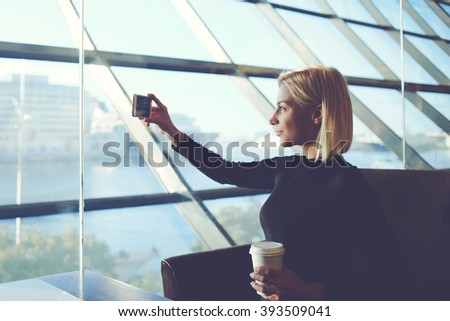 Young hipster girl is photographing herself on cell telephone, while is relaxing in modern coffee shop near sea port. Attractive woman with take away coffee is taking pictures with smart phone camera - stock photo