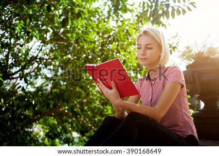 Young hipster girl reading her favorite book while she is relaxing in the fresh air during spring weekend,gorgeous blonde female is learning outdoors while sitting in beautiful green park in sunny day