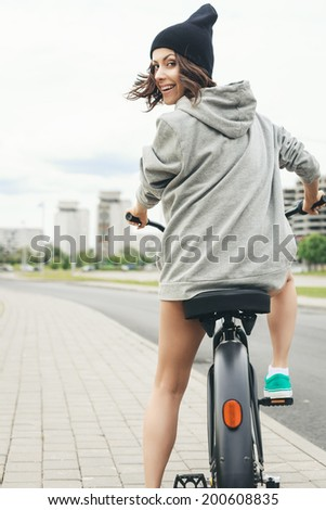 Young hipster girl with black bike back to camera. Outdoor lifestyle portrait - stock photo