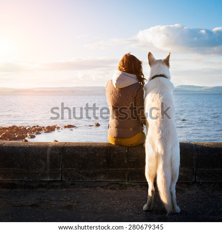Young hipster girl with her pet dog at a seaside, colorised image - stock photo