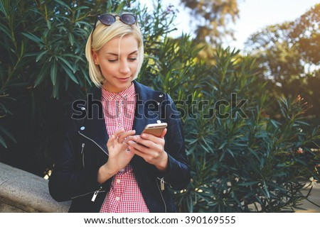 Young hipster girl with trendy look chatting on smart phone while resting in park in spring day, stylish female student searching information in network while sitting at the campus during class break - stock photo