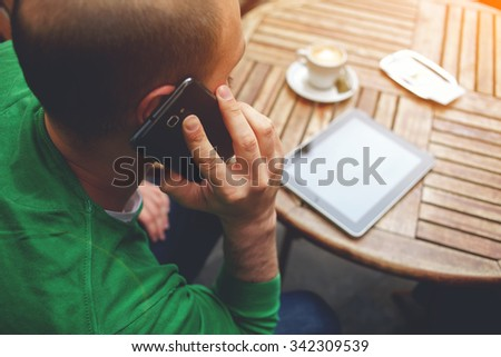 Young hipster guy having having conversation on mobile phone while sitting at the table with touch pad, man talking on cell telephone while rest after work on digital tablet with copy space screen - stock photo