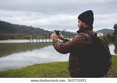 Young hipster guy taking photo on his mobile phone camera of a beautiful landscape while standing near lake, bearded man shoots video on cell telephone during amazing travel through the countryside - stock photo