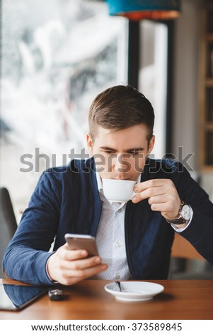 Young hipster guy texting with his mobile phone at the bar and having a cappuccino.Young fashion man / hipster drinking espresso coffee in city cafe during lunch time and working on tablet computer - stock photo
