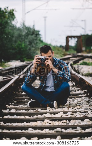 Young hipster guy tourist with camera and bag photographing on the railroad. Vintage Instagram style effect, soft and selective focus, grain texture visible on maximum size - stock photo