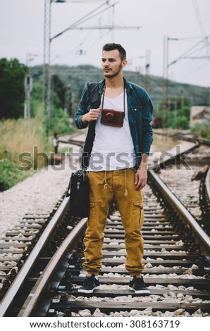 Young hipster guy tourist with camera and bag standing on the railroad. Vintage Instagram style effect, soft and selective focus, grain texture visible on maximum size - stock photo