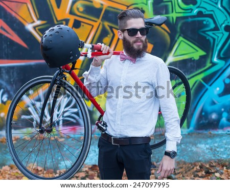 Young hipster guy with his bicycle posing. - stock photo