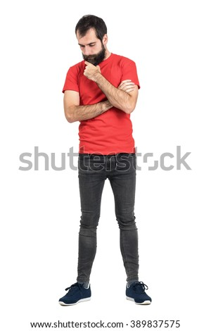 Young hipster in red t-shirt stroking beard white thinking and looking down. Full body length portrait isolated over white studio background. - stock photo
