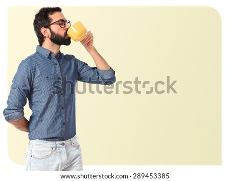 Young hipster man drinking coffee over textured background