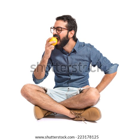 Young hipster man eating apple over white background - stock photo