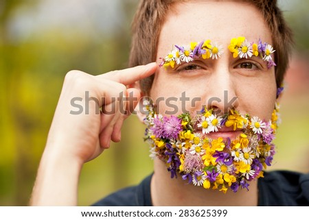 young hipster man face-covered with flowers makes an hand gesture meaning he wants you to think about environment and green power - stock photo