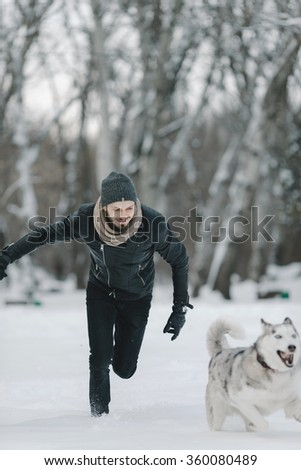 Young hipster man having fun in winter park on a bright day with his friend husky dog  - stock photo