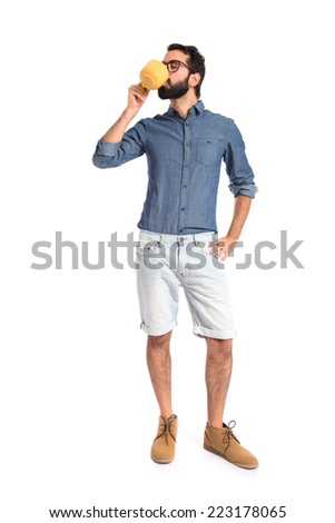 Young hipster man holding a cup of coffee - stock photo