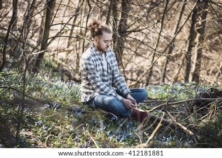Young hipster man in a plaid shirt sitting in the spring forest on the Scilla Siberia flower bed